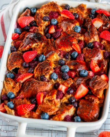 Baked Overnight Berry French Toast in white casserole dish on wire rack