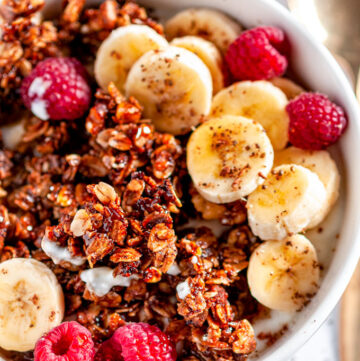 Crunchy Walnut Banana Bread Granola in white bowl with raspberries, sliced bananas, and gold spoon