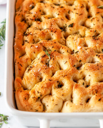 Easy Herbed Focaccia Bread in white baking dish with rosemary and oregano on white marble