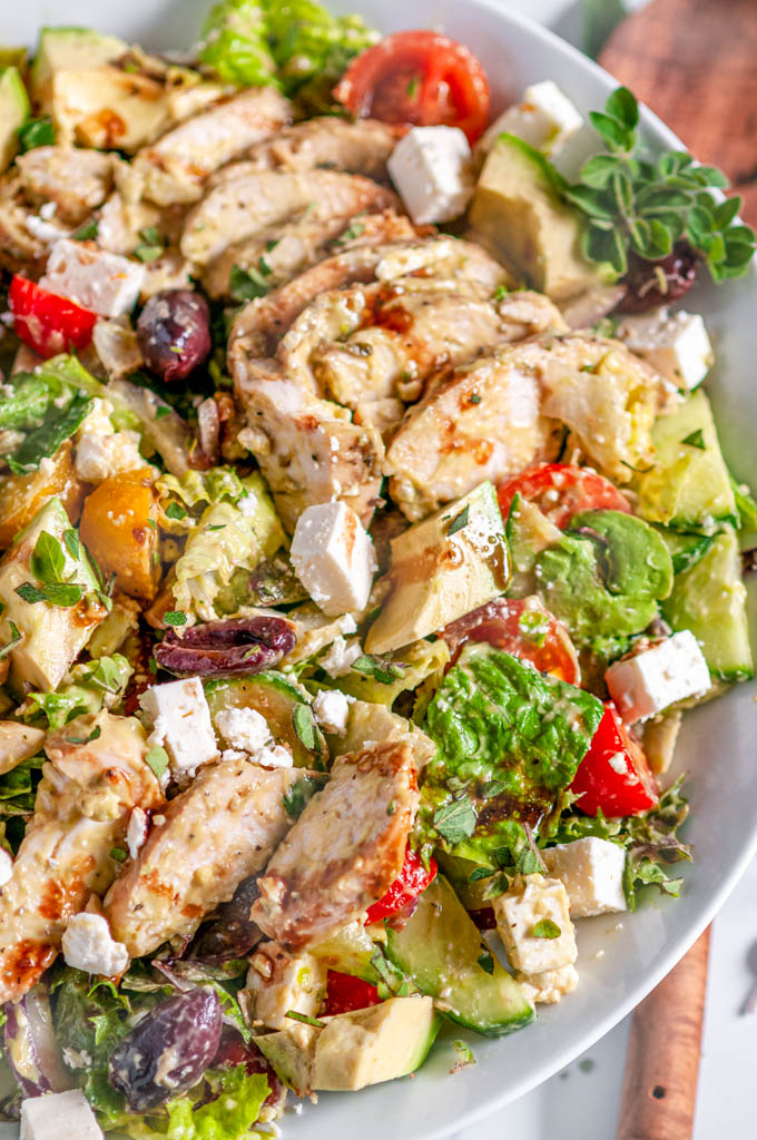 Greek Avocado Chicken Salad in white bowl on white marble with wooden spoon close up