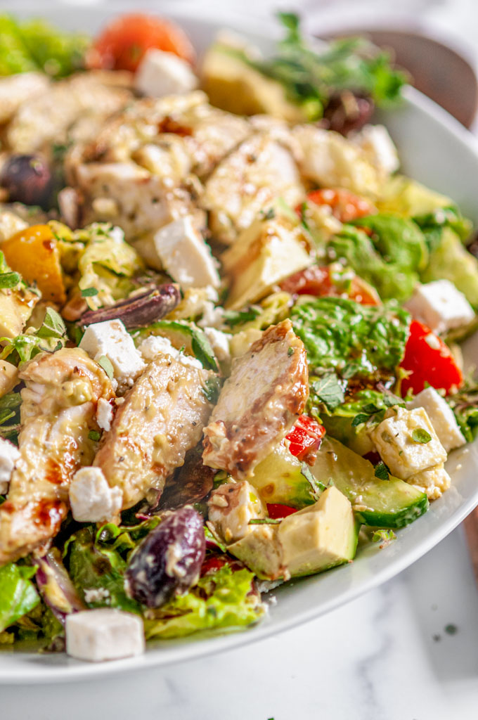 Greek Avocado Chicken Salad in white bowl on white marble close up