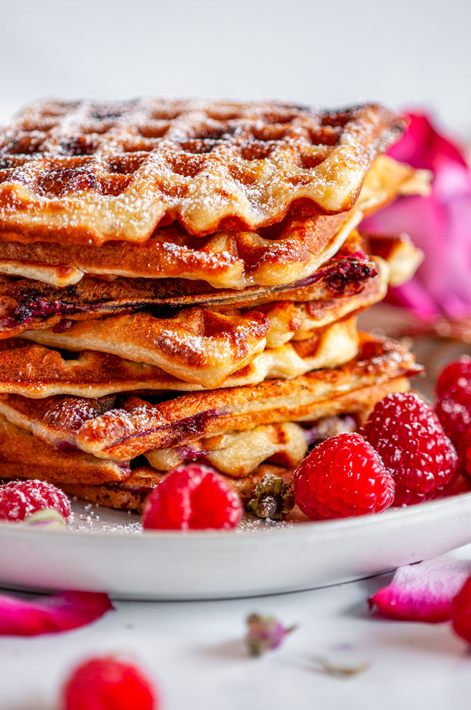 Lemon Raspberry Buttermilk Waffles stack with rose buds and petals on gray plate and white marble