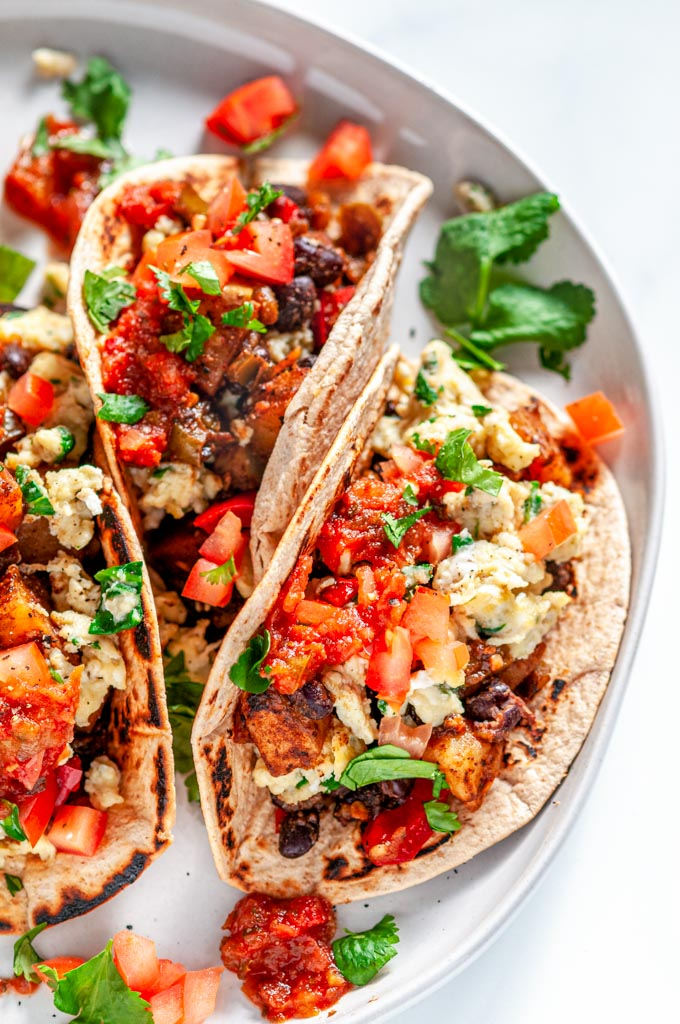 Loaded Vegetarian Breakfast Tacos with eggs, potatoes, black beans, salsa, and cilantro on white plate