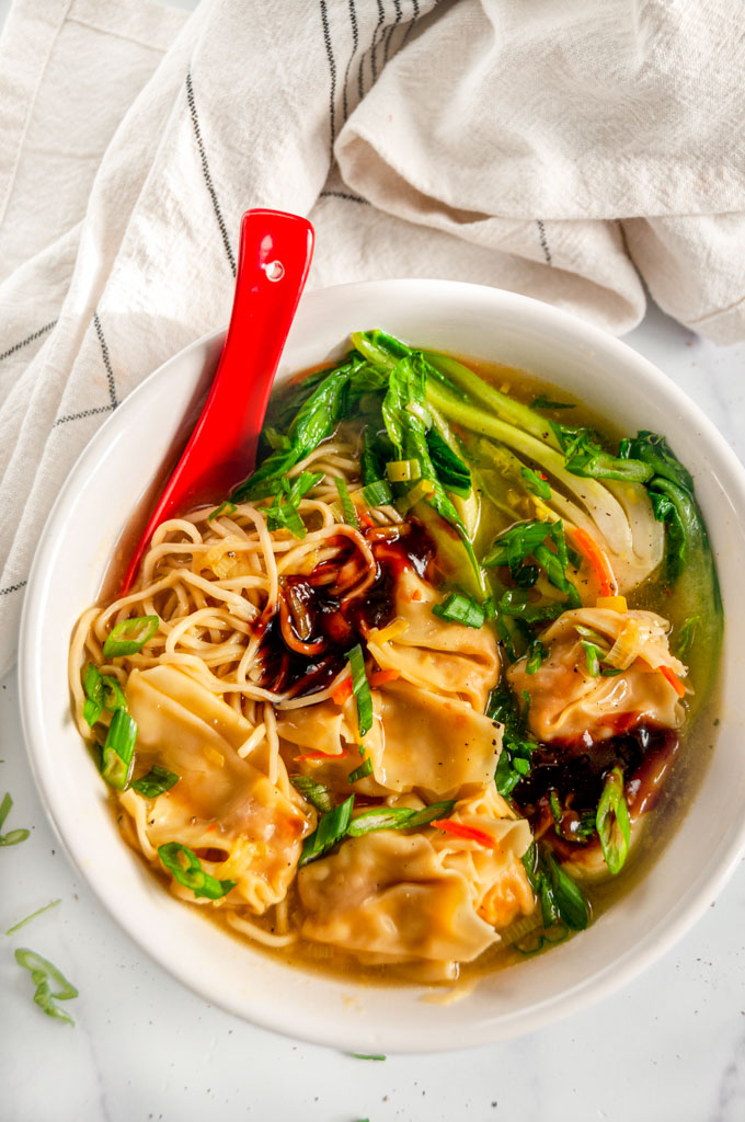 Quick 20 Minute Wonton Soup in white bowl with red spoon on marble