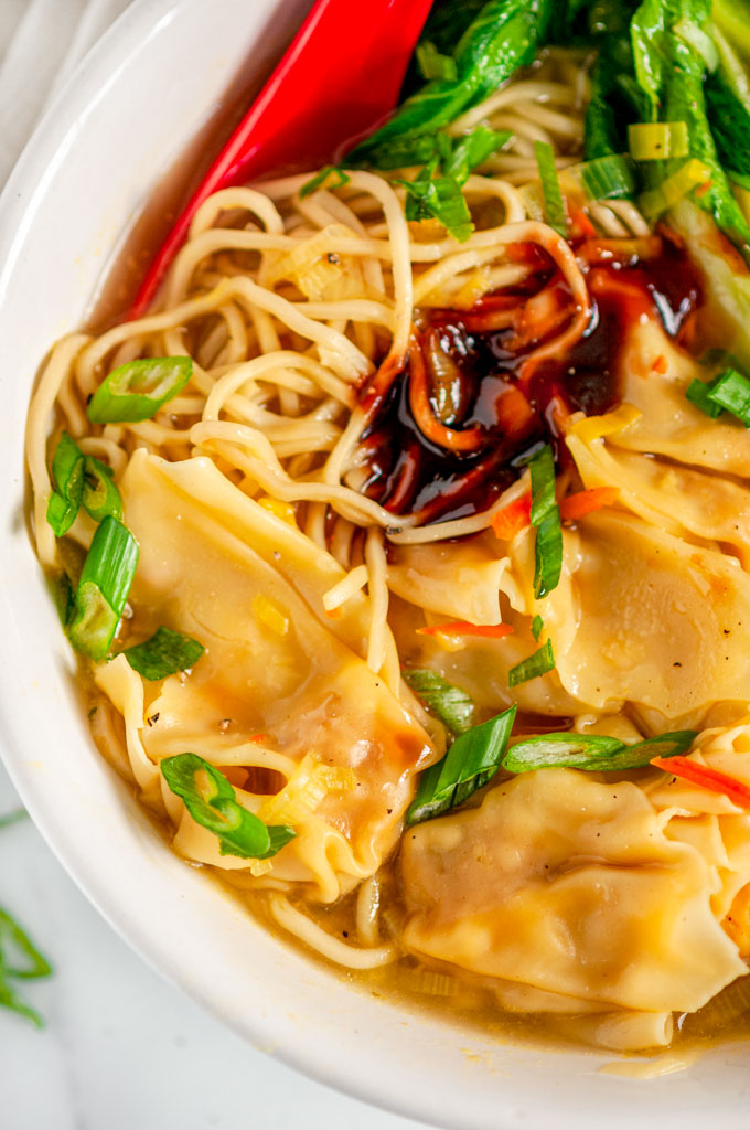 Quick 20 Minute Wonton Soup in white bowl with red spoon on marble close up