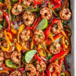 Sheet Pan Shrimp Fajitas with limes and bell peppers on baking pan