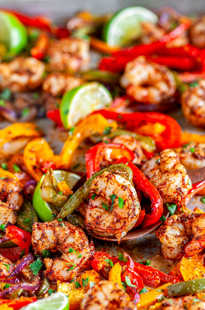 Sheet Pan Shrimp Fajitas with limes and bell peppers on baking pan close up