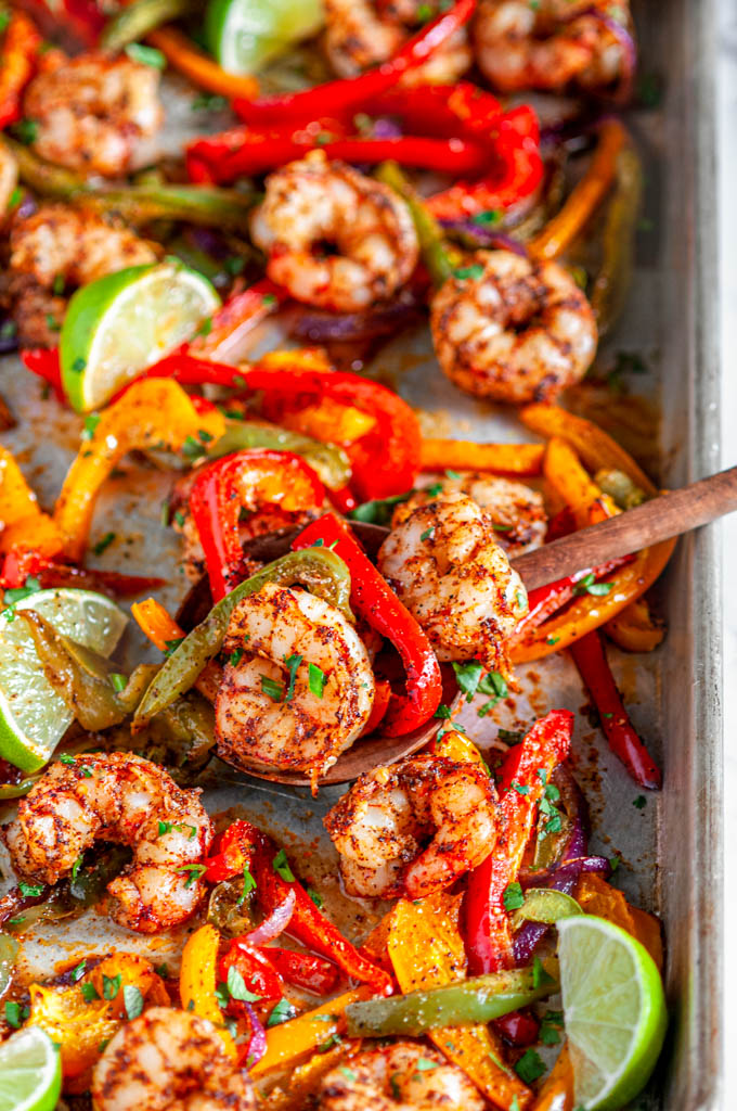 Sheet Pan Shrimp Fajitas with limes and bell peppers and wooden spoon on baking pan Sheet Pan Shrimp Fajitas with limes and bell peppers on baking pan