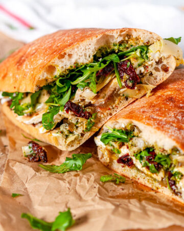 Kale Pesto Artichoke Caprese Sandwich on brown parchment paper and white marble