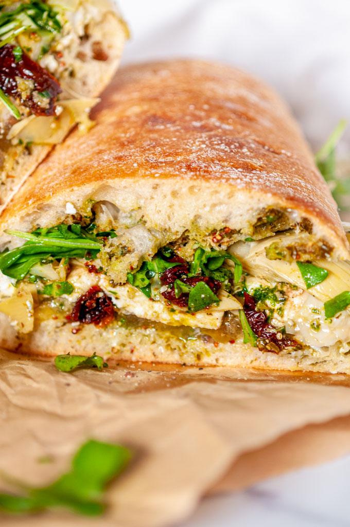Kale Pesto Artichoke Caprese Sandwich on brown parchment paper and white marble close up