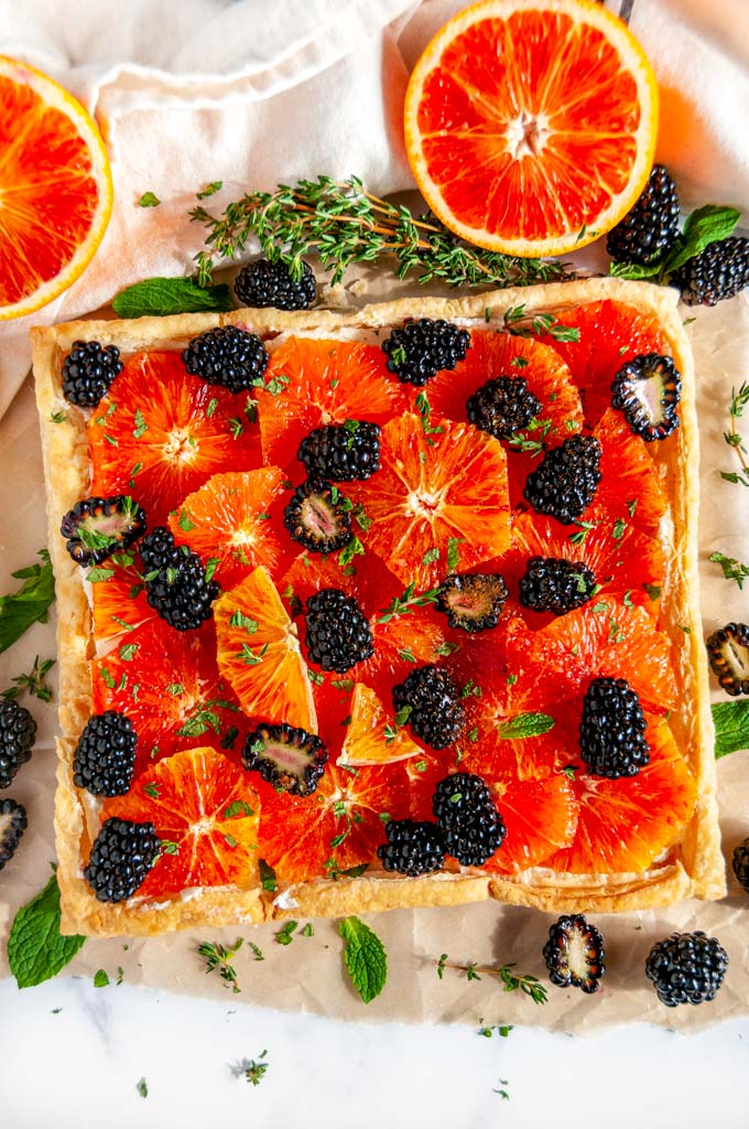 Blood Orange Blackberry Mascarpone Tart on brown parchment with fresh thyme and mint leaves