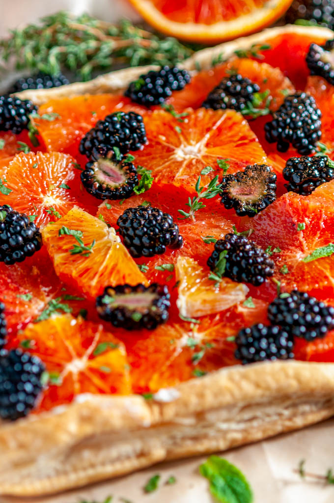 Blood Orange Blackberry Mascarpone Tart on brown parchment with fresh thyme and mint leaves close up