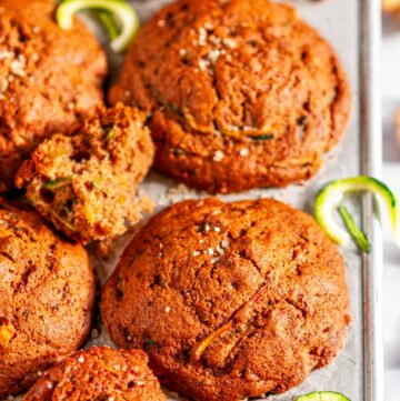 Breakfast Zucchini Walnut Muffins in tin muffin pan on white marble with tea towel close up