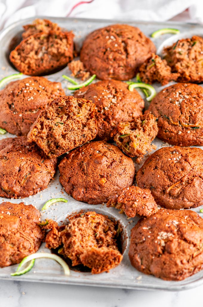 Breakfast Zucchini Walnut Muffins in tin muffin pan on white marble with tea towel