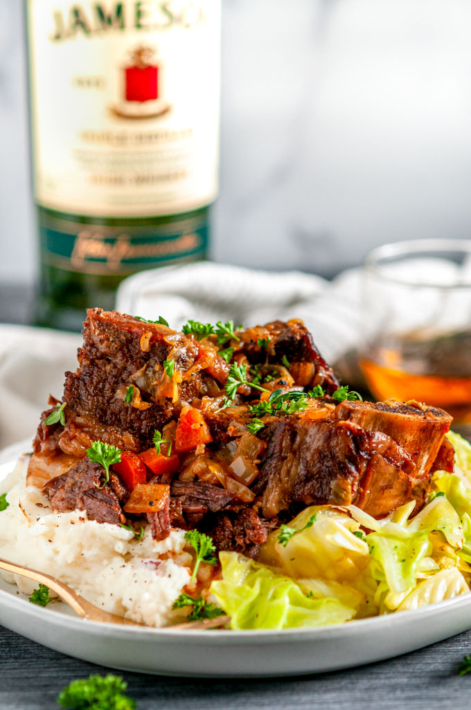 Instant Pot Whiskey Braised Short Ribs on gray plate with Jameson in a glass, mashed potatoes and cabbage