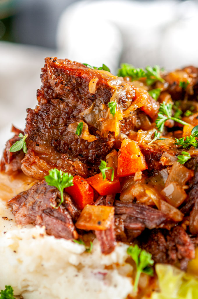 Instant Pot Whiskey Braised Short Ribs on gray plate mashed potatoes and cabbage close up