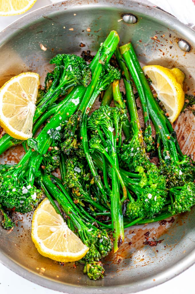 Quick and Easy Lemon Garlic Broccolini in skillet with lemon wedges and tea towel