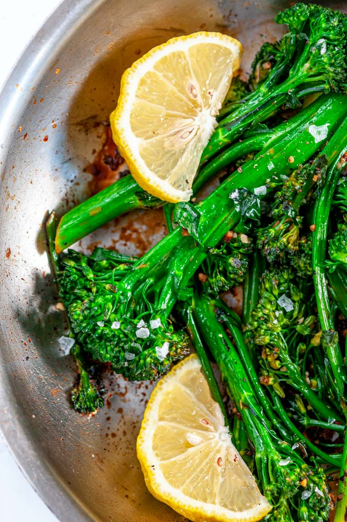 Quick and Easy Lemon Garlic Broccolini in skillet with lemon wedges close up