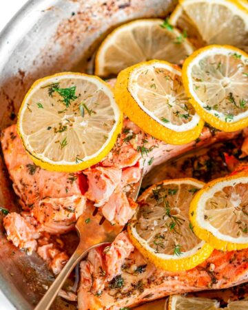 Skillet Lemon Dill Baked Salmon flaked with gold fork in All-Clad skillet