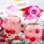 Sparkling Raspberry Senorita Margarita in rose sugar rimmed glasses with pink umbrellas on a gray plate, El Jimador tequila bottle in background