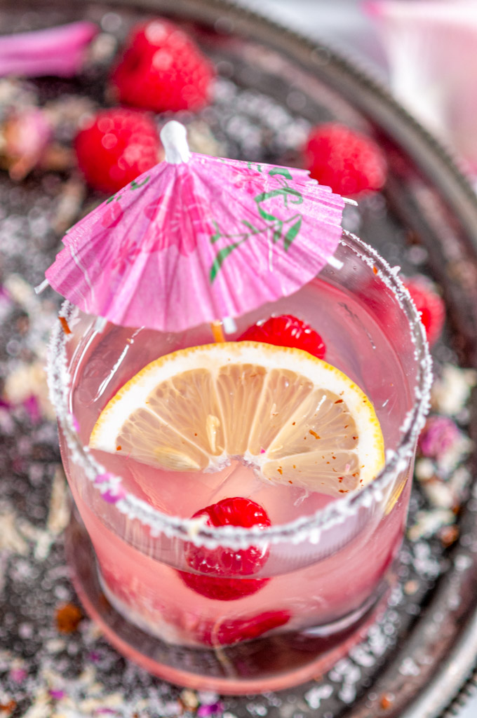 Sparkling Raspberry Senorita Margarita in rose sugar rimmed glass with pink umbrella on a gray plate