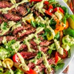 Steak Fajita Salad with Cilantro Avocado Dressing in white bowl on marble with lime slices and copper serving ware