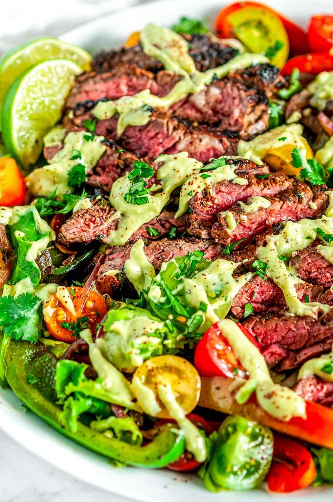 Steak Fajita Salad with Cilantro Avocado Dressing in white bowl on marble with lime slices