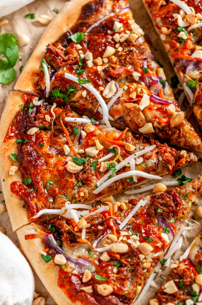 Thai Chicken Pizza on brown parchment paper cut into slices close up
