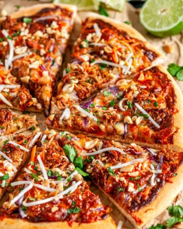 Thai Chicken Pizza on brown parchment paper cut into slices with lime slices