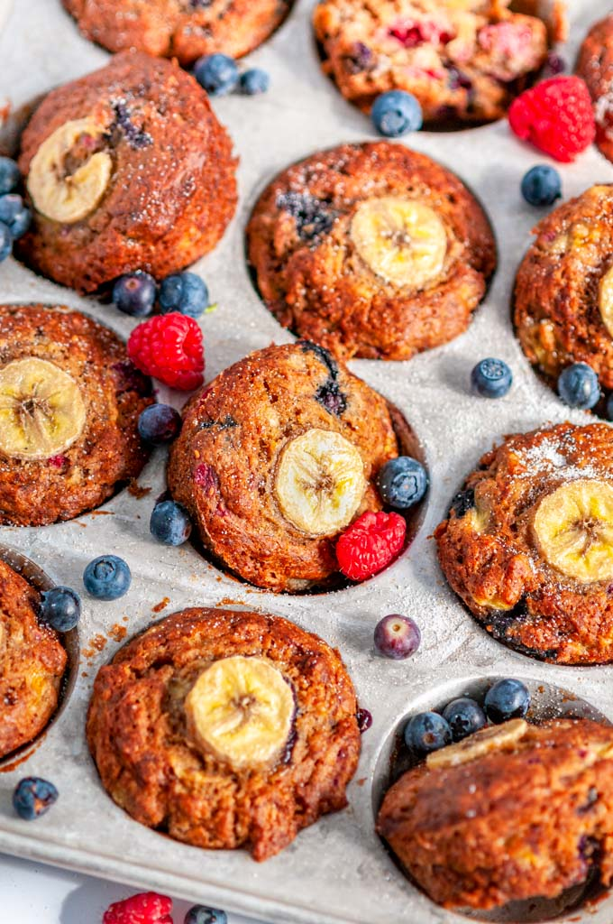 Banana Bread Berry Muffins in gray 12 muffin baking pan with blueberries and raspberries