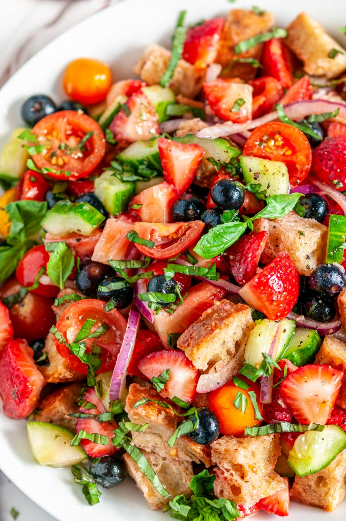 Berry Tomato Panzanella Salad in white bowl on marble close up
