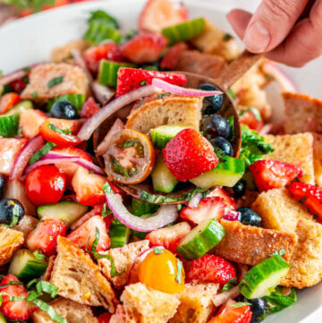 Berry Tomato Panzanella Salad in white bowl on marble with wooden spoon held in hand