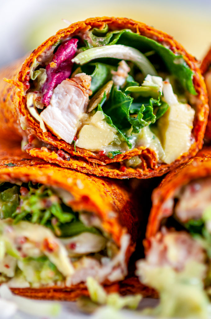 Healthy Chicken Avocado Wraps with kale salad mix on white plate