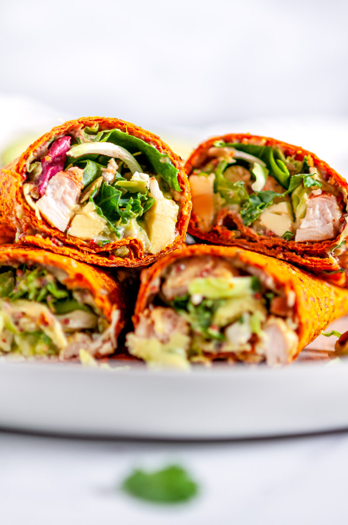 Healthy Chicken Avocado Wraps with kale salad mix on white plate and marble