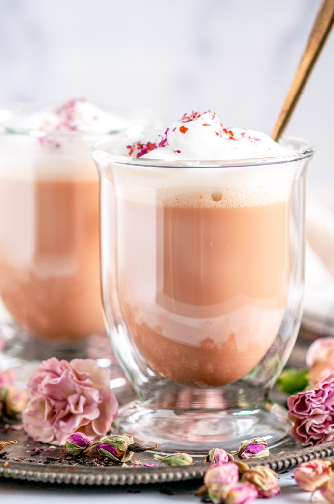 Rose Bud Earl Grey Tea Latte in glass mugs with gold spoons and pink flowers on gray plate