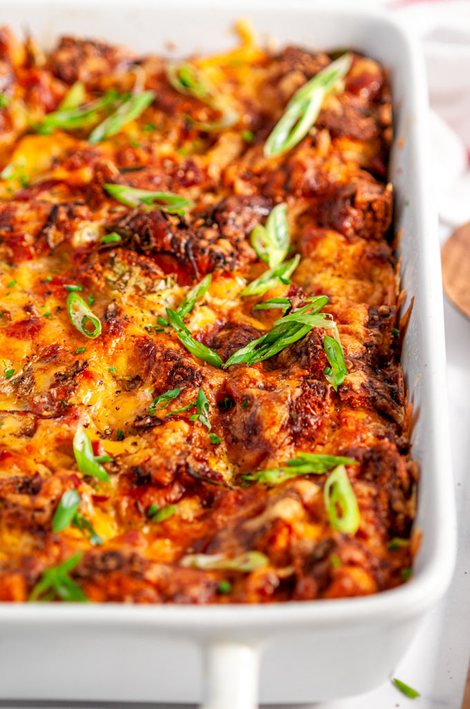 Savory Overnight Cheesy Ham Breakfast Casserole in white baking dish on marble with wooden spoon