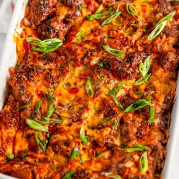 Savory Overnight Cheesy Ham Breakfast Casserole in white baking dish on marble with tea towel