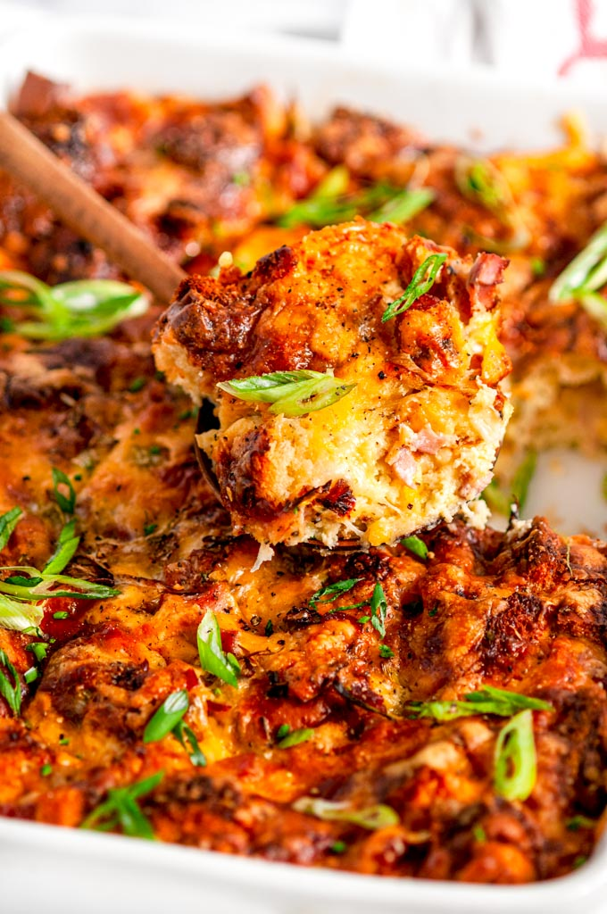 Savory Overnight Cheesy Ham Breakfast Casserole in white baking dish with wooden spoon holding slice close up