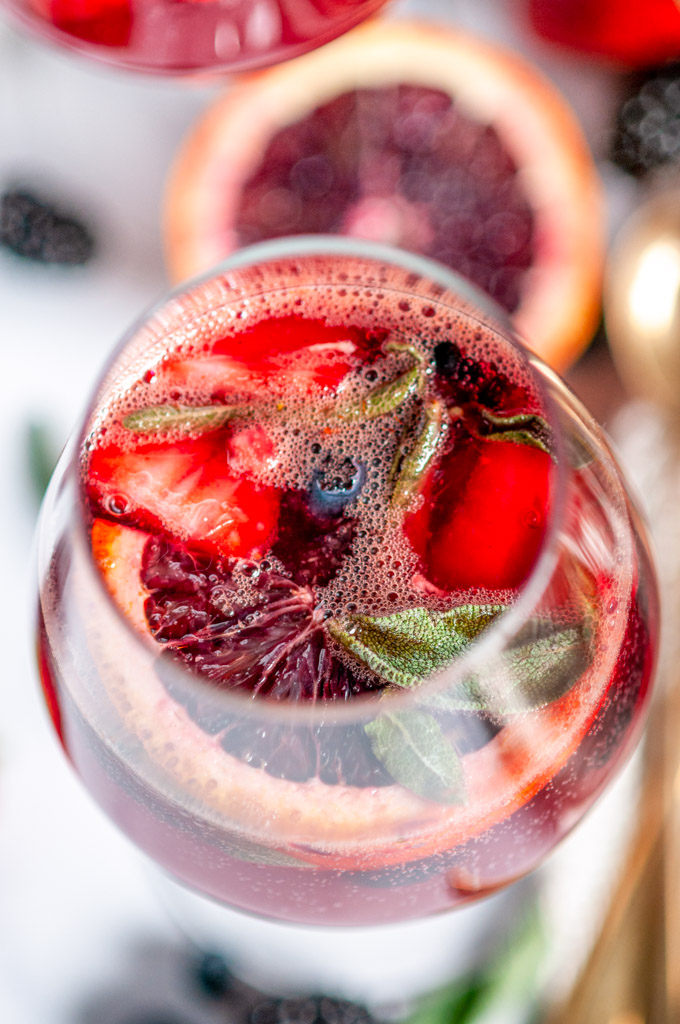 Sparkling Rosé Blood Orange Sangria with fresh sage leaves in glass on white marble close up