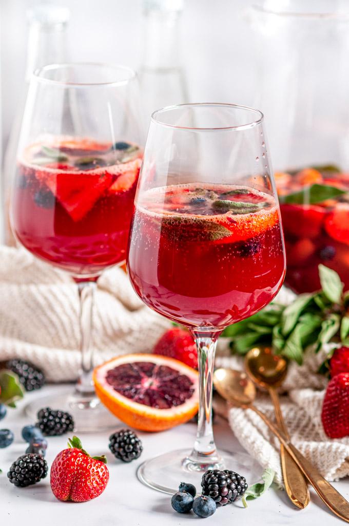 Sparkling Rosé Blood Orange Sangria with fresh sage leaves in glasses on white marble
