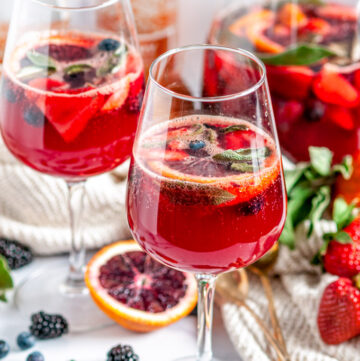 Sparkling Rosé Blood Orange Sangria with fresh sage leaves in glasses on white marble