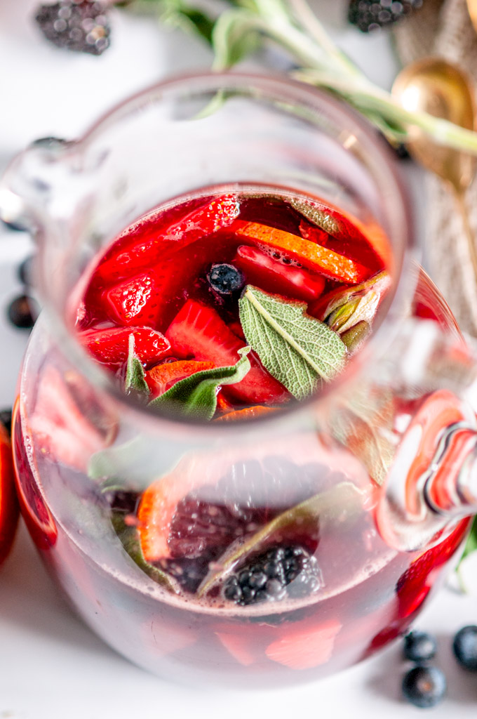 Sparkling Rosé Blood Orange Sangria with sage leaves in glass pitcher on white marble