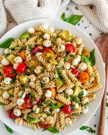 Caprese Pesto Pasta Salad in white bowl with wood spoon on marble