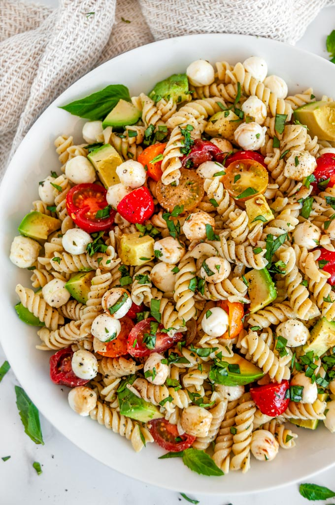 Caprese Pesto Pasta Salad in white bowl on marble