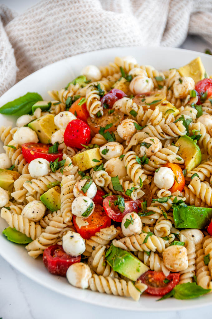 Caprese Pesto Pasta Salad in white bowl on marble