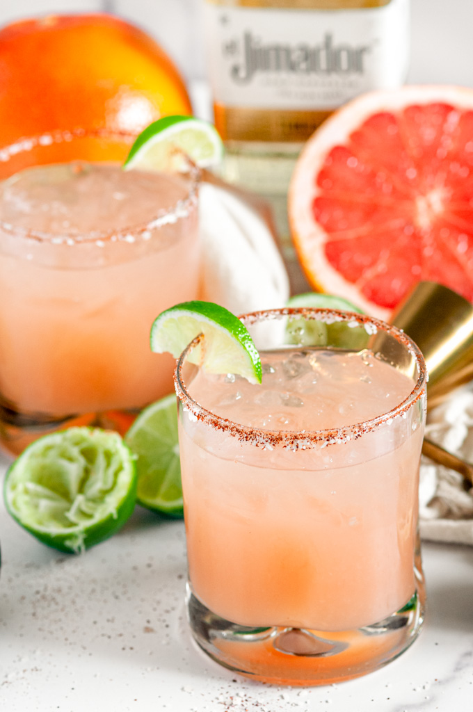 Classic Fresh Grapefruit Paloma in chili salt rimmed glasses and El Jimador tequila bottle in the background on white marble