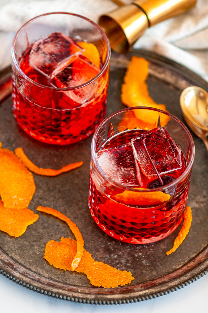 Classic Negroni Cocktail in two glasses with ice, orange peels, gold jigger, and tea towel