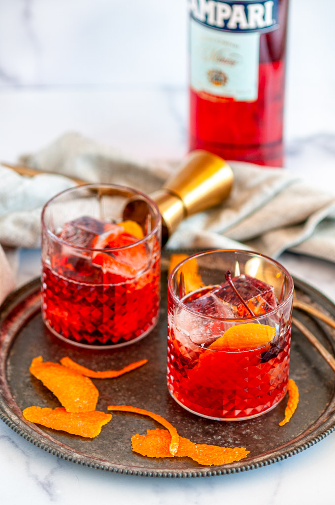 Classic Negroni Cocktail in two glass on gray plate with ice, orange peels, gold jigger, and Campari bottle in background
