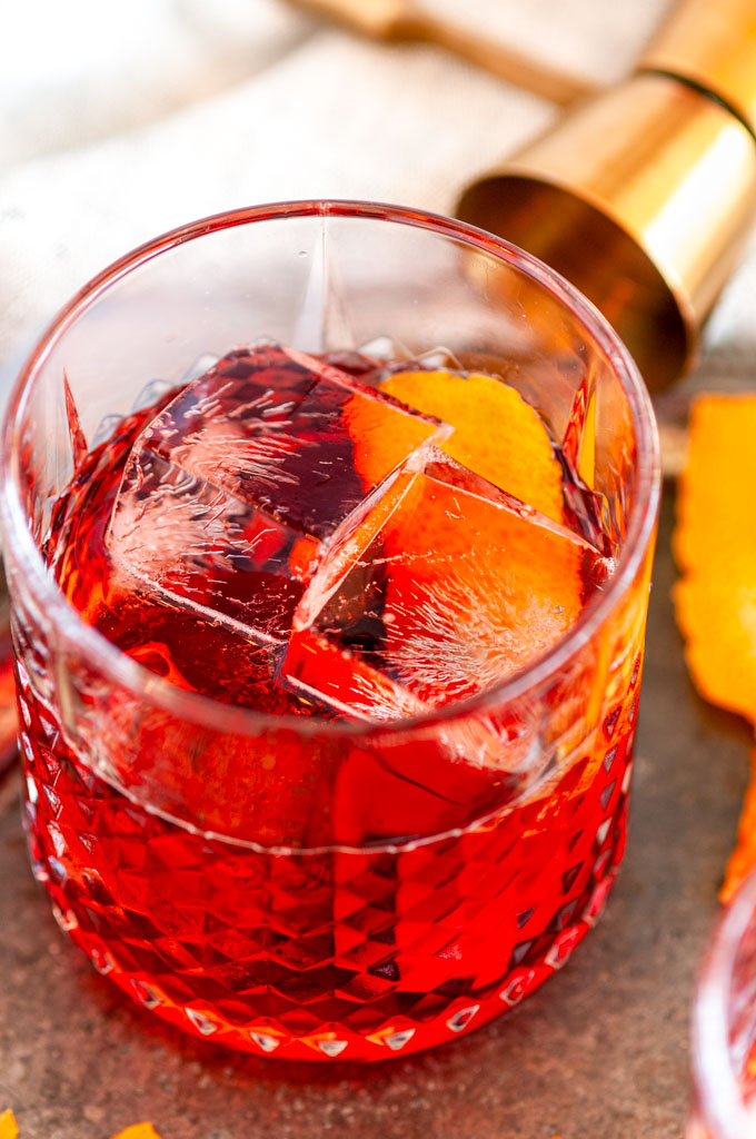 Classic Negroni Cocktail with ice, orange peels, gold jigger, and tea towel