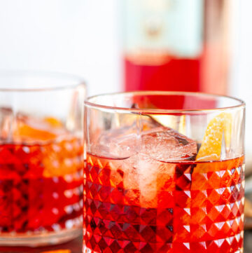 Classic Negroni Cocktail in two glass with ice, orange peels and Campari bottle in background